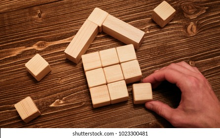 Man complete wooden model of the house with last piece. Property insurance protection concept. Building concept