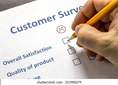 Man completing a customer survey with check boxes selecting to show his dissatisfaction