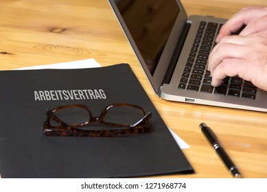 A man at the computer and a folder with the german word for employment contract