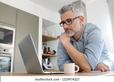 Man with computer at home in modern kitchen