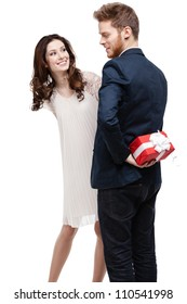 Man conceals the present behind the back from his pretty girlfriend, isolated on white