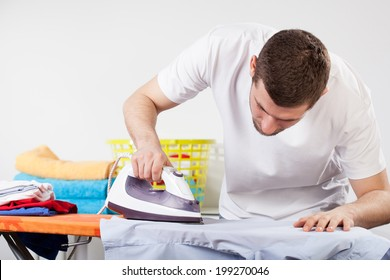 A man concentrated on ironing a shirt