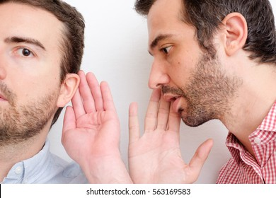 Man confessing a secret to another one in the ear