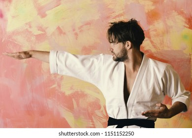Man with confident face and bristle on colorful background. Karate fighter with fit strong body practices martial arts. Guy poses in white kimono with black belt. Healthy lifestyle and jujitsu concept