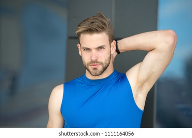 Man confident in his antiperspirant. Sportsman after training pleased with antiperspirant. Guy checks dry armpit satisfied with healthy skin. Prevent, reduce perspiration. No sweat - deodorant works.