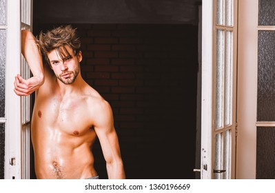 Man confident lover near door. Sexy bachelor lover concept. Sexy attractive macho tousled hair coming out through bedroom door. Guy attractive lover posing seductive. Seductive lover full of desire.