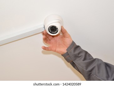 The man configures the surveillance camera on a room ceiling