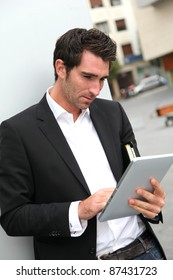 Man connected on internet with electronic tablet in town