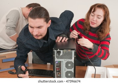 The man connects the new computer, and the woman helps.