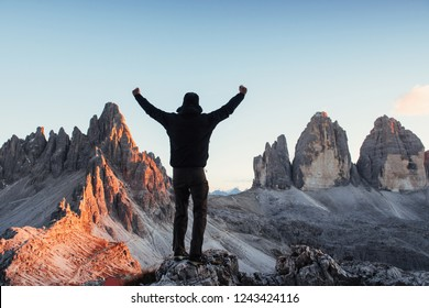 Man conquering the hill and show hands while standing on the stone in the front of Paternkofel and Tre Chime mountains