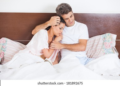 Man consoles his wife lying bed in bedroom, couple consoling, husband embrace comforts his woman