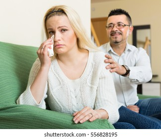 Man consoling depressed crying young woman on sofa at home