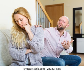 Man consoling the depressed woman on sofa at home Focus on girl