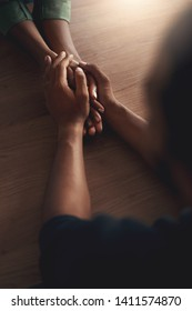 Man consoling girlfriend by holding her hands