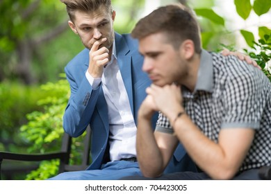 Man consoling sadness friend he closing his face, crying and feeling upset cause from his mistake in the park.Breakup concept