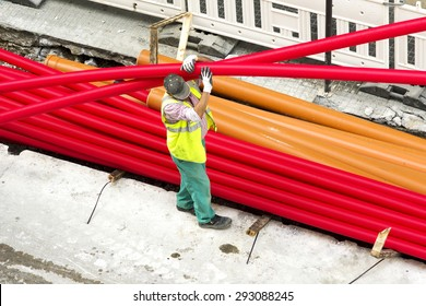 man construction worker placing   kg sewer pipe  and  corrugated conduit  pìpe  in  construction site