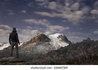 Man contemplates the last rays of the sun on the snowy mountain at sunset