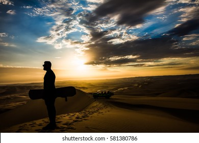 A man contemplating the incredible colors of the sunset, alone with his sandboard preparing himself for action.