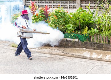 Man control Mosquito sprayer killing insects and fogging to eliminate mosquito for preventing spread dengue fever and zika virus.Worker fogging residential area with chemical.