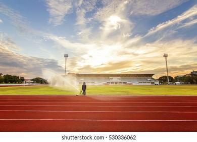 Man control Sprinkler watering to grass field in stadium