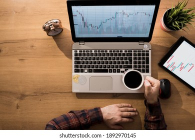 Man controlling cryptocurrency traffic with laptop from home. The man who earns bitcoin is comfortably drinking coffee.
