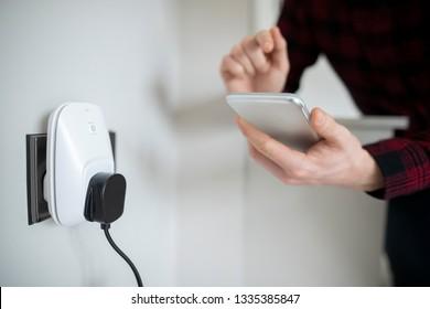 Man Controlling Smart Plug Using App On Mobile Phone