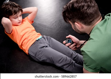 man controlling time while boy doing press exercise on black