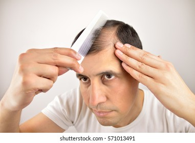 man controls hair loss with a comb