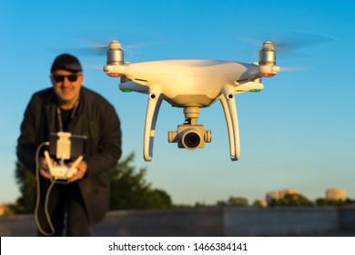 A man controls a quadcopter. Hobby launching drones. Unmanned aerial vehicles. Quadcopter takes off from the ground. Photo and video from the drone.