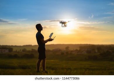 The man controls a quadrocopter on the sunset background