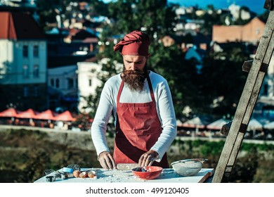 Man cook chef hipster with long beard on handsome face in red hat and apron white uniform rolling dough with pin outdoor near ladder on natural background