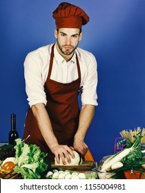 Man in cook hat and apron cuts cabbage. Cook works in kitchen near table with vegetables and tools. Chef with sexy face chops cabbage with knife on blue background. Kitchenware and cooking concept.