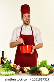 Man in cook hat and apron mixes in pot. Food preparation concept. Chef with excited face holds red saucepan on white background. Cook works in kitchen near table with vegetables and tools.