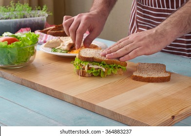 Man cooking big sandwich with chicken on a wooden table in the rustic kitchen