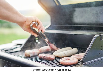 Man cooking different meat with professional barbecue grill in backyard outdoor - Concept of bbq party with families and friends - Focus on hand - Warm filter with back sun light