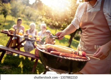 Man are cooking for family and they are having barbecue party in garden on summer.