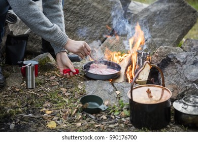 Man Cooking Food Over Bonfire At Campsite