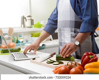 Man cooking in the kitchen and learning new recipes, he is connecting with a laptop and slicing fresh vegetables