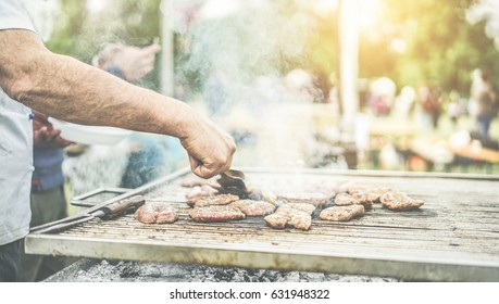 Man cooking meat at dinner barbecue - Chef grilling meat in park outdoor - Concept of eating bbq outdoor during summer time - Focus on left man hand - Warm vintage filter with back sunlight