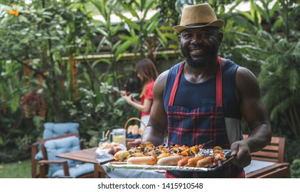 Man cooking meat on barbecue grill for Group of friends at summer outdoor party and holidays concept.