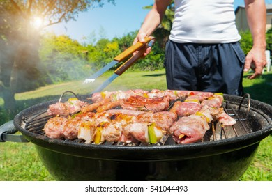 Man cooking meat on a barbecue grill
