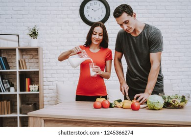 Man is Cooking Salad. Woman is Pouring a Milk in Cup from Jar. Woman is a Pregnant Girl. Man is Cutting the Pepper a Knife. Vegetables and Salad in Bowl on Table. People Located at Home.