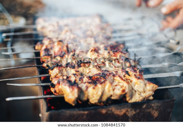 man cooking shashlyk outdoor, fried meat on grill, nature, rest time, summer