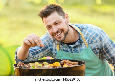 Man cooking tasty food on barbecue grill outdoors