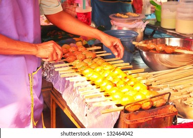 A man cooking Thai style meatball on grilled
