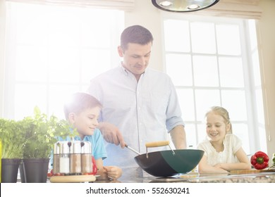 man cooking with a wok in the kitchen
