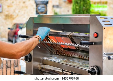 A man cooks the Arrosticini, skewers of sheep meat, a typical dish of Abruzzo cuisine, on a gas grill, in a stall of a village festival. Grilled meat, barbeque. Street food.