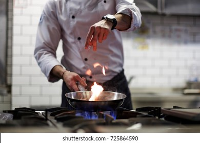 A man cooks cooking deep fryers in a kitchen fire. He gently fry the vegetables while cooking the dish.