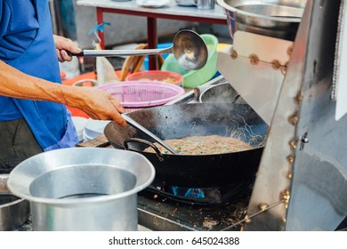 Man cooks stir-fried noodles at Kimberly Street Food Night Market in George Town, Penang, Malaysia.