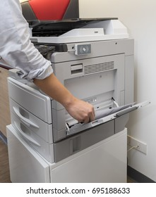 Man copying inserting paper from Photocopier with access control for scanning key card